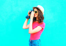 Fashion pretty woman taking picture wearing straw summer hat, sunglasses and vintage camera over colorful blue Stock Photos