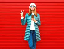 Fashion pretty woman using smartphone holds in hands on a red. Background in the city Royalty Free Stock Images