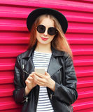 Fashion pretty woman using smartphone in rock black style over colorful pink royalty free stock image