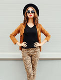 Fashion pretty woman wearing black hat, sunglasses and jacket over urban background Stock Photos