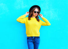 Fashion pretty woman wearing a black hat and yellow knitted sweater over colorful blue. Background Royalty Free Stock Photo