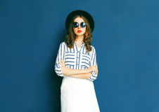 Fashion pretty woman wearing a black sunglasses, hat and white skirt Stock Photos