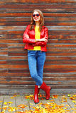 Fashion pretty woman wearing a red leather jacket and rubber boots in autumn yellow leafs Royalty Free Stock Images