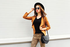 Fashion pretty woman wearing a retro elegant hat, sunglasses, brown jacket and black handbag walking in city over background Royalty Free Stock Images