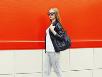 Fashion pretty woman wearing a rock black leather jacket, sunglasses and bag in profile Royalty Free Stock Photos