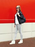 Fashion pretty woman wearing a rock black leather jacket, sunglasses and bag walking in city Royalty Free Stock Photo