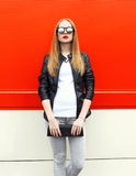 Fashion pretty woman wearing a rock black leather jacket, sunglasses and handbag clutch. Over red background Royalty Free Stock Photo