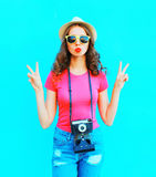 Fashion pretty woman wearing straw summer hat, sunglasses and vintage camera over colorful blue Stock Photos