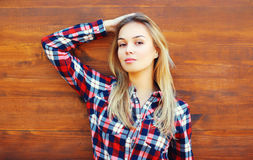 Fashion pretty woman wearing a sunglasses and checkered shirt over wooden. Background Royalty Free Stock Images