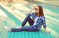 Fashion pretty woman wearing a sunglasses and checkered shirt. Sitting in city Stock Photo