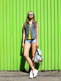 Fashion pretty woman wearing a sunglasses and jeans clothes. With backpack over colorful green wall Stock Image