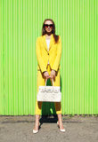 Fashion pretty woman in yellow suit clothes with handbag posing. Against the colorful green wall royalty free stock images