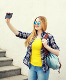 Fashion pretty young girl makes selfie portrait on smartphone Stock Photography