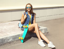 Fashion pretty young girl with skateboard and backpack outdoors Stock Images