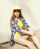 Fashion pretty young girl wearing a cap and checkered shirt Royalty Free Stock Image