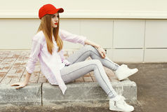 Fashion pretty young girl wearing a shirt and red cap Stock Photos