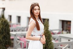 Fashion pretty young girl in white dress on the street royalty free stock image