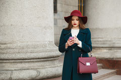 Fashion pretty young lady wears hat and coat in classic style use smartphone. Royalty Free Stock Images