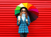 Fashion pretty young smiling woman with colorful umbrella coffee cup wearing a black hat coat jacket over red Stock Image