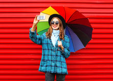 Fashion pretty young smiling woman with colorful umbrella taking picture self portrait on smartphone wearing black hat coat jacket Royalty Free Stock Image