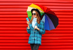 Fashion pretty young smiling woman with colorful umbrella using smartphone wearing a black hat coat jacket over red Stock Photo