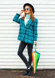 Fashion pretty young smiling woman with colorful umbrella wearing a black hat checkered coat jacket over white Stock Images