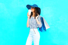 Fashion pretty young smiling woman is drinks coffee from cup wearing a shopping bags, straw hat, white pants over colorful blue Stock Photography