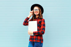 Fashion pretty young smiling woman holding laptop computer or tablet pc in city, wearing a black hat, red checkered shirt Royalty Free Stock Photography