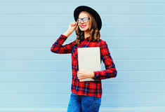 Fashion pretty young smiling woman holding laptop computer or tablet pc in city, wearing black hat, red checkered shirt over blue. Background Stock Images