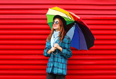 Fashion pretty young smiling woman holds colorful umbrella wearing black hat checkered coat jacket over red Stock Images