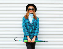 Fashion pretty young smiling woman holds colorful umbrella wearing black hat checkered coat jacket over white Royalty Free Stock Photos
