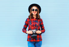 Fashion pretty young smiling woman holds retro camera wearing black hat red checkered shirt over blue background Royalty Free Stock Photo