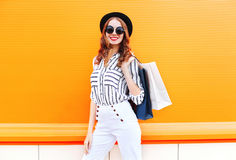 Fashion pretty young smiling woman model with shopping bags wearing a black hat white pants over colorful orange. Background Stock Images