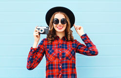 Fashion pretty young smiling woman and retro camera wearing a black hat, red checkered shirt over blue Stock Photo