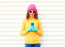 Fashion pretty young smiling woman using smartphone wearing colorful knitted clothes over white Royalty Free Stock Images