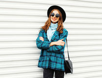 Fashion pretty young smiling woman wearing black hat coat jacket with handbag over white. Background Stock Image