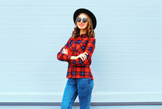 Fashion pretty young smiling woman wearing black hat, red checkered shirt over blue background. Fashion pretty young smiling woman wearing a black hat, red Royalty Free Stock Photo