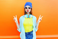 Fashion pretty young woman is blowing her red lips in the city over colorful orange Royalty Free Stock Image
