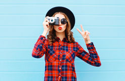 Fashion pretty young woman blowing red lips with retro camera wearing a black hat, red checkered shirt over blue Stock Image