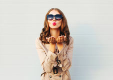 Fashion pretty young woman blowing red lips sends sweet kiss wearing a black sunglasses coat over grey Royalty Free Stock Images
