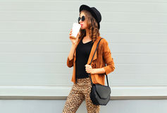 Fashion pretty young woman drinks coffee of cup wearing a retro elegant hat, sunglasses, brown jacket and black handbag Stock Photo