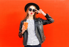 Fashion pretty young woman with fresh fruit juice cup in black rock style having fun over colorful red Stock Photos