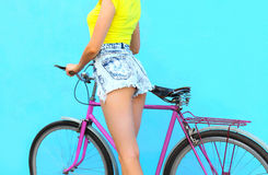 Fashion pretty young woman in jeans shorts on bicycle over colorful blue background Royalty Free Stock Photos
