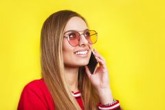 Fashion pretty young woman model in sunglasses using smartphone. Fashion pretty young woman model in sunglasses and red dress using smartphone Royalty Free Stock Photos