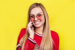 Fashion pretty young woman model in sunglasses using smartphone. Fashion pretty young woman model in sunglasses and red dress using smartphone Royalty Free Stock Images
