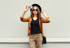 Fashion pretty young woman model taking photo picture self-portrait on smartphone wearing retro elegant hat, sunglasses. Brown jacket and handbag with curly Royalty Free Stock Photography