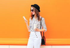 Fashion pretty young woman model using smartphone with coffee cup wearing black hat white pants over colorful orange Royalty Free Stock Photo