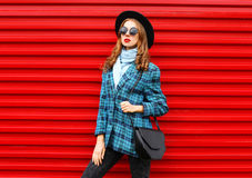 Fashion pretty young woman model wearing black hat coat jacket with handbag over colorful red Stock Images