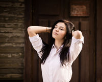 Fashion pretty young woman posing near a old wooden wall. Stock Image