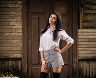 Fashion pretty young woman posing outdoor near a old wooden wall.  Stock Photos